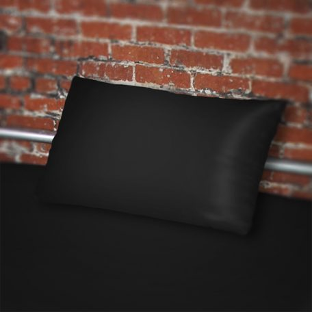 Black pillowcase on black fluidproof sheet against a brick wall
