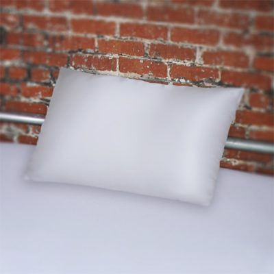 White Fluidproof Pillowcase on white bedsheets set against a brick wall