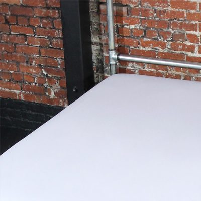 White Fluid-proof Flat Sheet on a galvanised bed frame against a brick wall