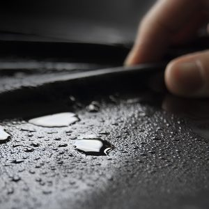 Fingers stoking the source of a black fluid proof sheet covered in moisture
