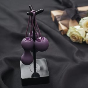 Purple Kegel Balls on a black metal stand on a backdrop of a black fuidproof sheet